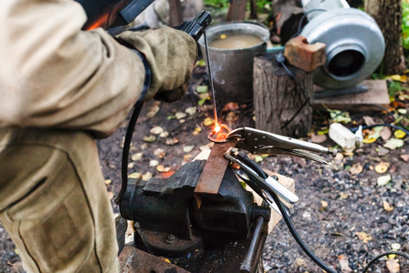 welds: Welder welds iron ring by spot electric welding in outdoor rural workshop