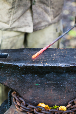 smithy: red hot glowing steel rod on anvil in outdoor rural smithy
