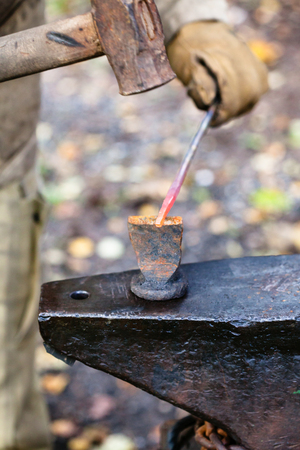 smithy: Blacksmith cut out hot metal rod with sledgehammer and chisel on anvil in outdoor rural smithy Stock Photo