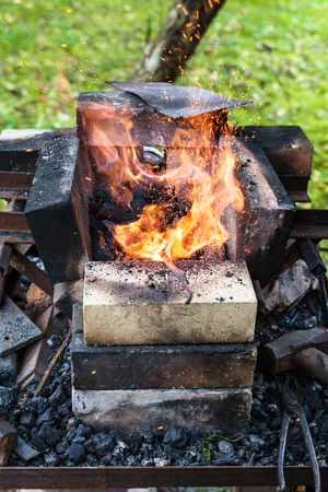 iron rod is heated in outdoor rural brick forging furnace in burning coals Stock Photo