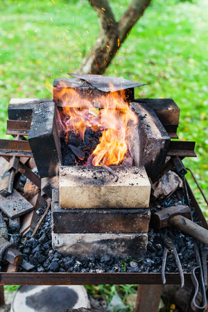 steel rod is heated in rural forging furnace in burning coals Stock Photo