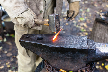 smithy: Blacksmith hammering hot steel rod on anvil in outdoor rural smithy