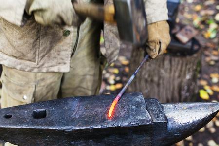 hammering: Blacksmith hammering red hot iron rod on anvil in outdoor rural smithy