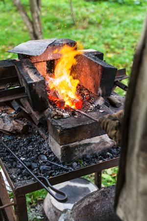 crucible: Blacksmith heats steel rod in rural forging furnace with burning coals