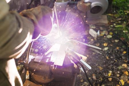 buckle: Welder welds steel buckle in outdoor rural workshop
