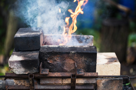crucible: flame in outdoor rural brick forging furnace during coal heating Stock Photo