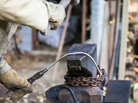 blacksmith forges iron rod on an anvil with a sledgehammer in outdoor rural smithy