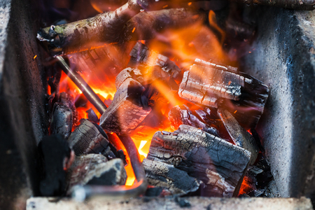 forge: iron rod is heated in burning wooden coals in the forge furnace close up Stock Photo