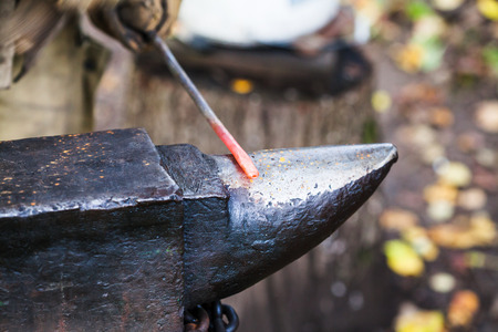 smithy: red hot heated iron rod on anvil in outdoor rural smithy Stock Photo