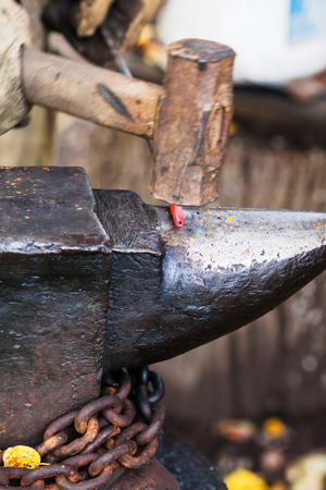 Blacksmith forges sizzling hot metal rod with sledgehammer on anvil in outdoor rural smithy