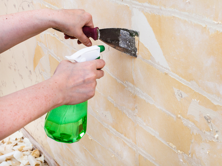wet wallpaper: renovation of room: preparation of walls. Cleaning wall from wet old wallpaper with metal spatula