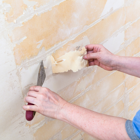 upholsterer: renovation of apartment: cleaning wall from paper backing before wallpapering Stock Photo