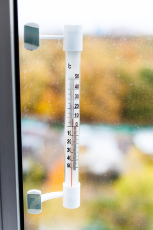 outdoor thermometer on home window glass in autumn day Stock Photo