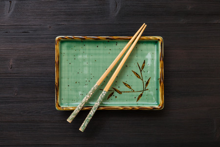 hashi: top view of one green square plate with chopsticks on dark brown table
