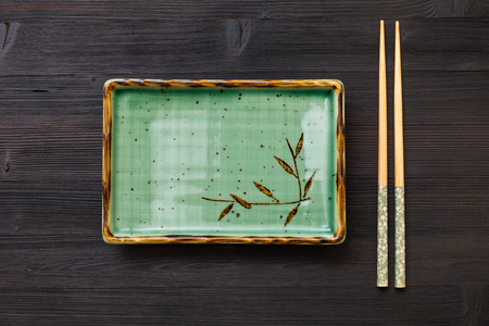 hashi: top view of one green square plate and chopsticks on dark brown board
