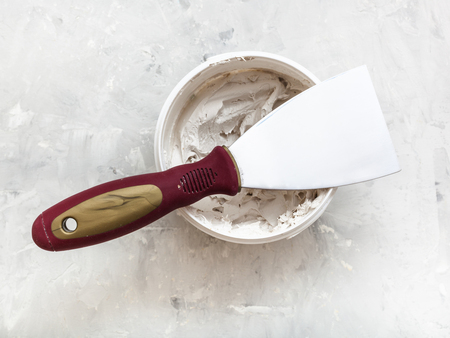 plasterer: metal spatula with plastic handle on container with putty on the concrete floor