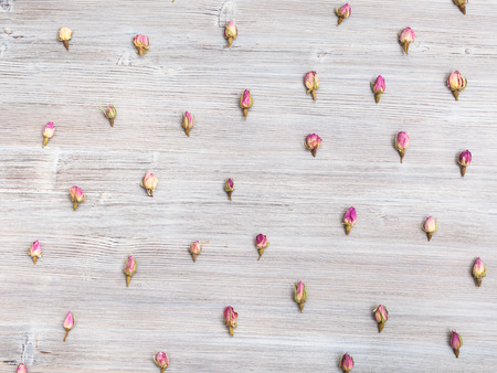 disordered: many natural pink rose flower buds on wooden table