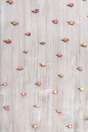 disordered: many natural pink rose flower buds on wooden surface Stock Photo