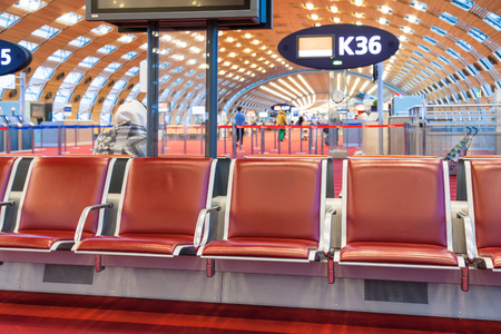 charles de gaulle: empty red seat in departure lounge of airport