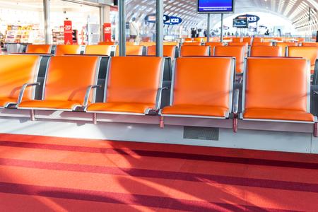 empty orange seat in departure hall of airport Stock Photo