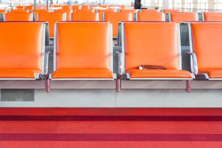 empty orange seat in departure lounge of airport
