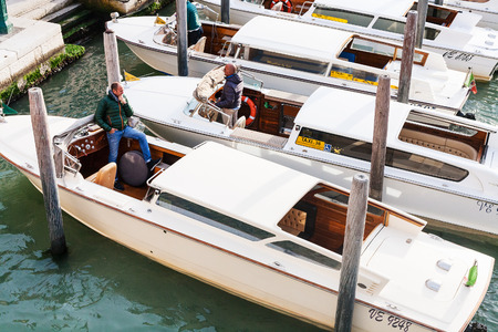 tariff: VENICE, ITALY - OCTOBER 11, 2016: awater taxis with drivers in canal of Venice city. A water taxi in Venice is expensive transportation - tariff from Airport tohotel in town is 100-110 euros