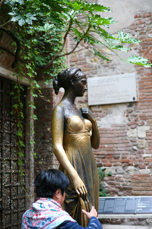 juliets: VERONA, ITALY - OCTOBER 10, 2016 - tourist near of Juliet statue in Juliets house in Verona city. Juliet's house (Casa di Giulietta) is one of the main tourist attractions of Verona