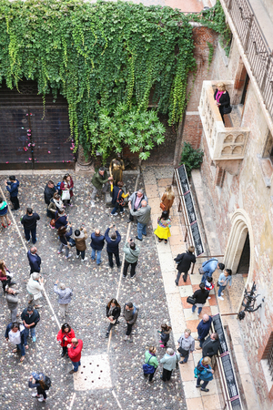 juliets: VERONA, ITALY - OCTOBER 10, 2016 - above view of balcony and tourists on yard of Juliets house in Verona city. Juliet's house (Casa di Giulietta) is one of the main tourist attractions of Verona