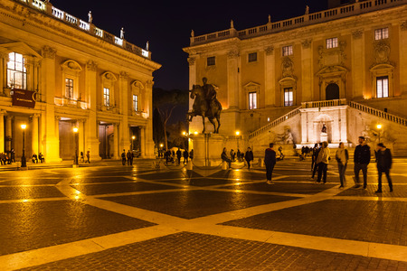 ROME, ITALY - OCTOBER 31, 2016: tourists on Piazza del Campidoglio on Capitoline hill of Rome city in night. The existing design of the square was created by Michelangelo Buonarroti in 1536-1546