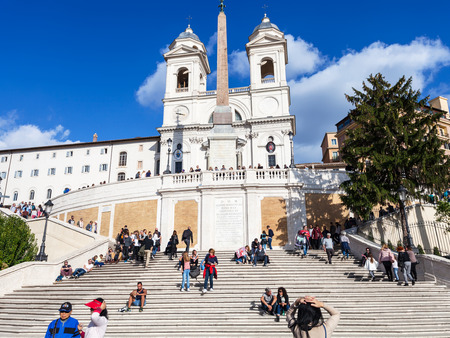 spanish steps: ROME, ITALY - NOVEMBER 1, 2016: people on Spanish Steps and Church Santissima Trinita dei Monti. The church is best known for its position above Spanish Steps which lead down to the Piazza di Spagna Editorial