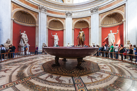 VATICAN, ITALY - NOVEMBER 2, 2016: visitors near statues, Hercules figure and round monolithic porphyry basin in Round Room of Pio-Clementino Museum in Vatican museums in Vatican city