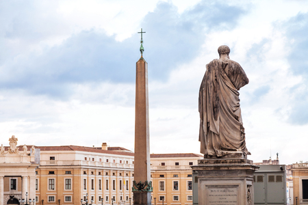 travel to Italy - view of statue the Apostle Peter and obelisk with cross on Saint Peters Square (Piazza San Pietro) in Vatican city in evening