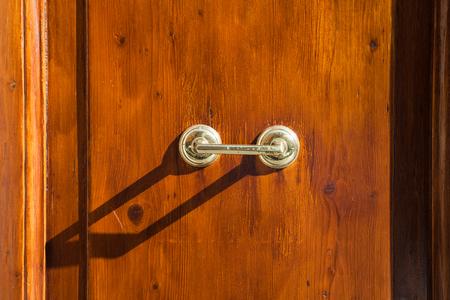 travel to Italy - old external brass door handle on brown wooden door in Rome city Stock Photo