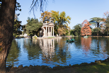 aesculapius: travel to Italy - walking boats on pond near Temple of Aesculapius in Villa Borghese public gardens in Rome city in autumn Foto de archivo