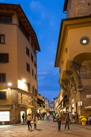 FLORENCE, ITALY - NOVEMBER 3, 2016: people near shops on Ponte Vecchio (Old Bridge) in Florence in evening. The Ponte Vecchio is medieval stone bridge noted for still having shops built along it