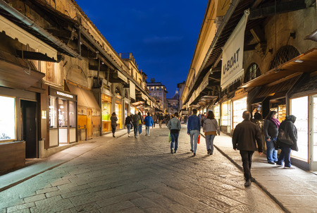 noted: FLORENCE, ITALY - NOVEMBER 3, 2016: tourists near shops on Ponte Vecchio (Old Bridge) in Florence in evening. The Ponte Vecchio is medieval stone bridge noted for still having shops built along it