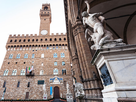 museum visit: FLORENCE, ITALY - NOVEMBER 4, 2106: Loggia dei Lanzi with statue (The Rape of the Sabine Women) and Palazzo Vecchio (Old Palace) in morning. The Palazzo Vecchio is the town hall of Florence city.
