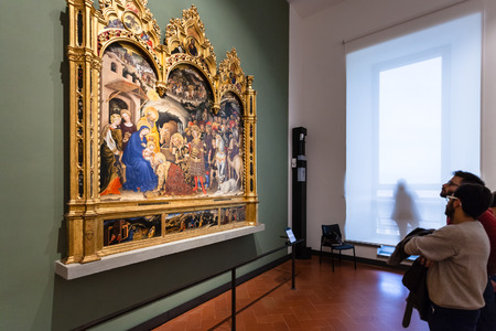 FLORENCE, ITALY - NOVEMBER 5, 2016: Visitors view painting in room of Uffizi Gallery. The Uffizi is one of the oldest museums in Europe, its origin refers to 1560, when Vasari designed large palace Editorial