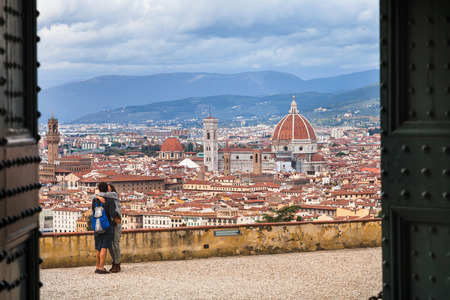 FLORENCE, ITALY - NOVEMBER 7, 2016: above view of tourists and Florence city through gate of Basilica San Miniato al Monte. This roman church stands atop one of the highest points in the city