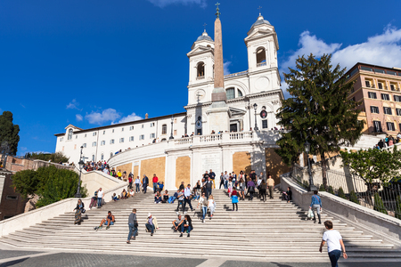 ROME, ITALY - NOVEMBER 1, 2016: tourists on Spanish Steps and Church Santissima Trinita dei Monti. The church is best known for its position above Spanish Steps which lead down to the Piazza di Spagna
