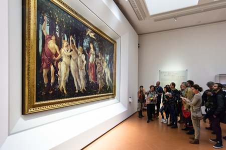 FLORENCE, ITALY - NOVEMBER 5, 2016: visitors in Botticelli hall of Uffizi Gallery. The Uffizi is one of the oldest museums in Europe, its origin refers to 1560, when Vasari designed large palace