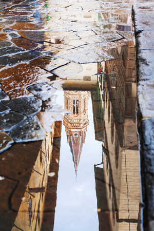 apartment tower old town: travel to Italy - tower of church Badia Fiorentina reflected in puddle on street after rain in Florence city Stock Photo