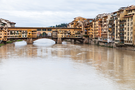 river arno: travel to Italy - Ponte Vecchio (Old Bridge) over Arno River and houses on quay in Florence city in autumn Stock Photo