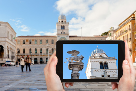travel concept - tourist photographs winged lion on piazza dei Signori in Padua city on tablet in Italy