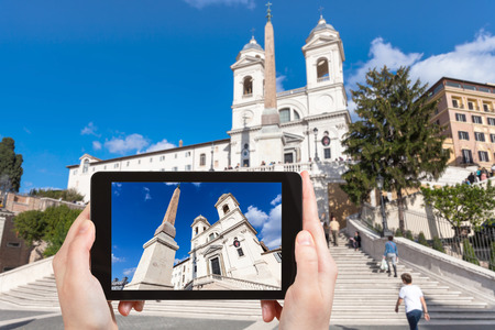 travel concept - tourist photographs Church Santissima Trinita dei Monti and Spanish Steps in Rome city on tablet in Italy