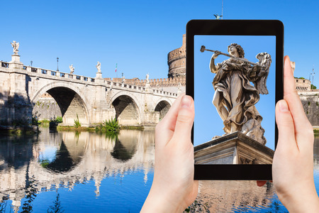 travel concept - tourist photographs Angel statue on bridge in Rome city on tablet in Italy Stock Photo