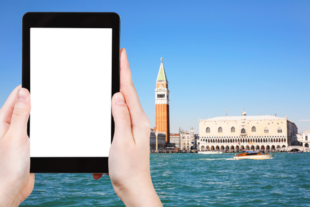 travel concept - tourist photographs Venice skyline on tablet with cut out screen with blank place for advertising in Italy