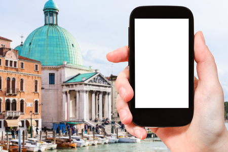 travel concept - tourist photographs Church San Simeone Piccolo in Venice city on smartphone with cut out screen with blank place for advertising in Italy