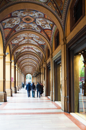 BOLOGNA, ITALY - OCTOBER 31, 2012: people in medieval arcade on piazza Cavour in Bologna city. The painting of the arcade vault was completed by Gaetano Lodi between 1862 and 1865 Editorial