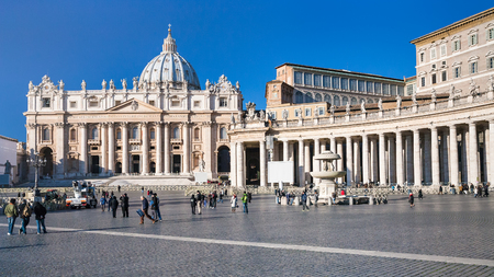 VATICAN, DECEMBER 16, 2010: tourists on Piazza San Pietro (St Peters Square) and view of St Peter Basilica in sunny winter day. Basilica is Catholic Cathedral, largest Christian church in world